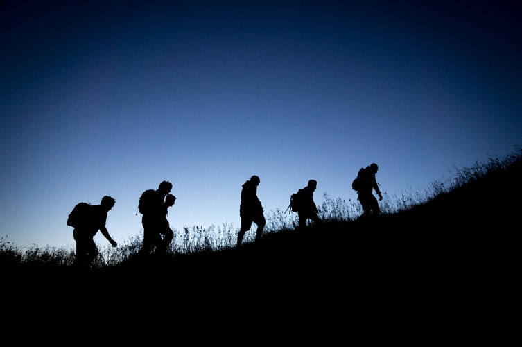 Silhouette of people hiking at night [image by Tobias Mrzyk]