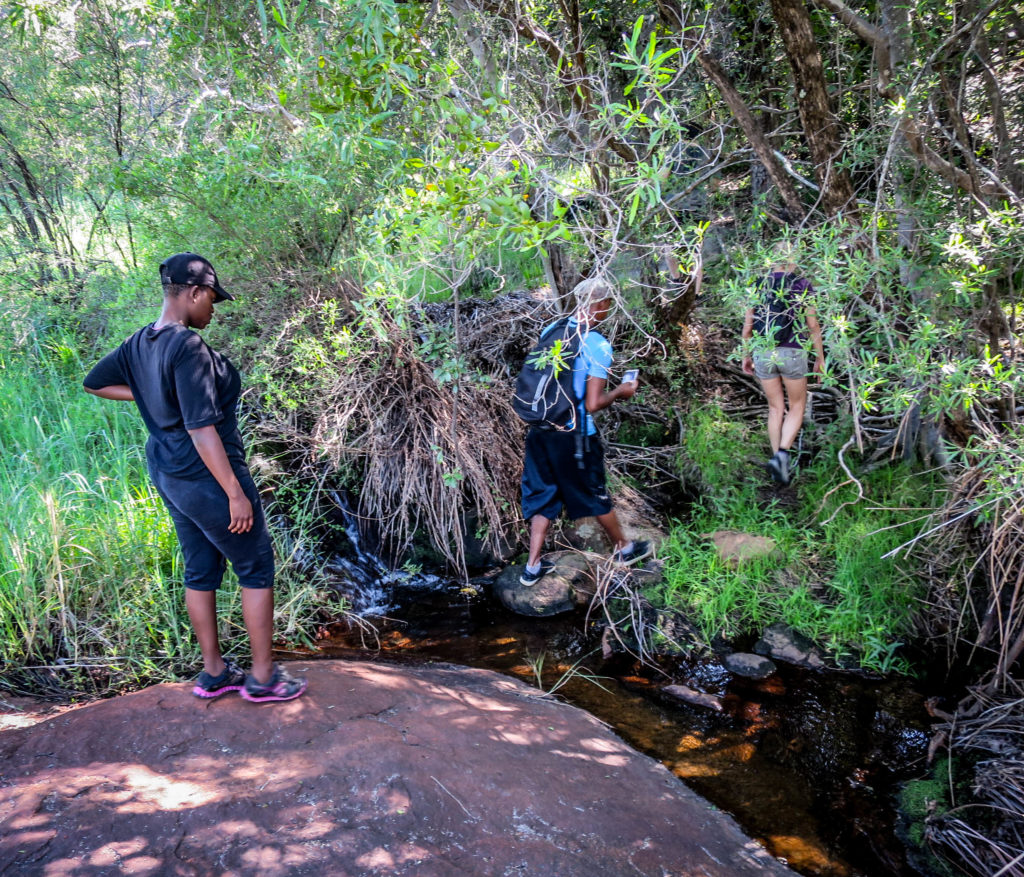 Finding their feet: Hikers crossing one of the many streams on the Inanke Trail in the Matopos National Park.Photo: Matobo Hills Lodge.
